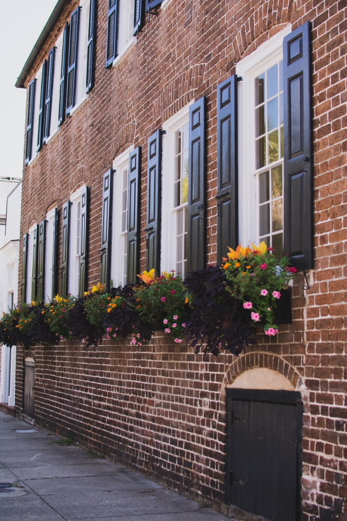 Historic house, brick with black shutters and colorful windowboxes